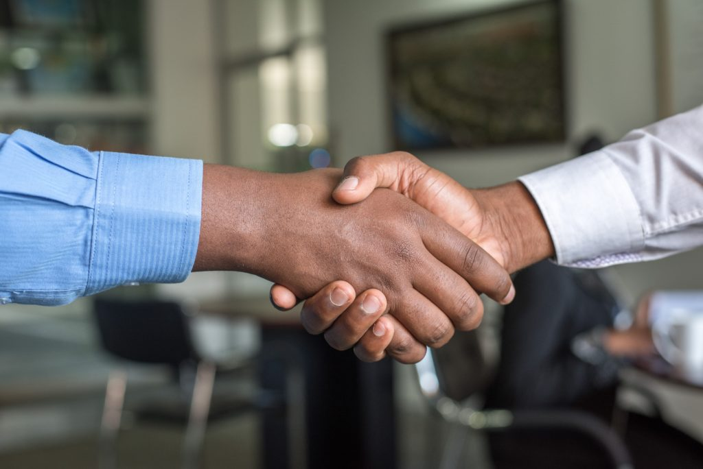 A candidate shakes hands upon accepting a position.