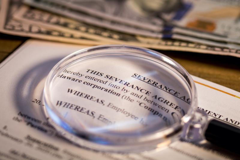 There are common questions about severance pay, as represented by a magnifying glass highlighting a severance agreement.
