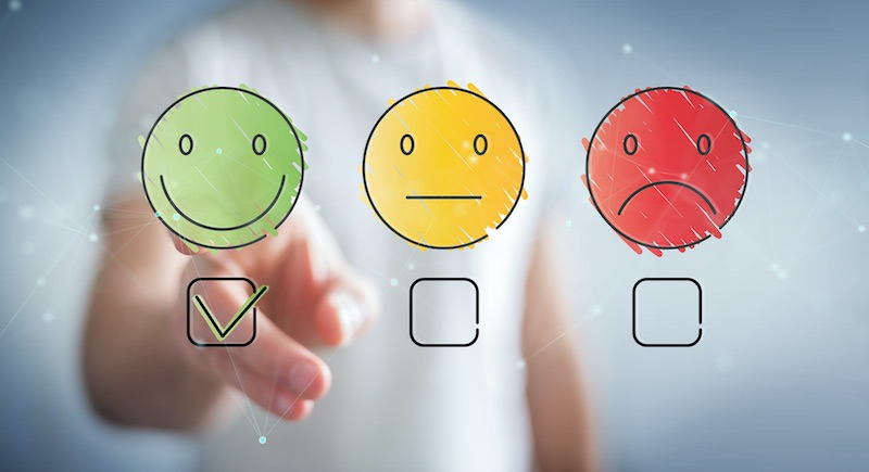 A blurred customer makes a positive selection on a satisfaction rating system