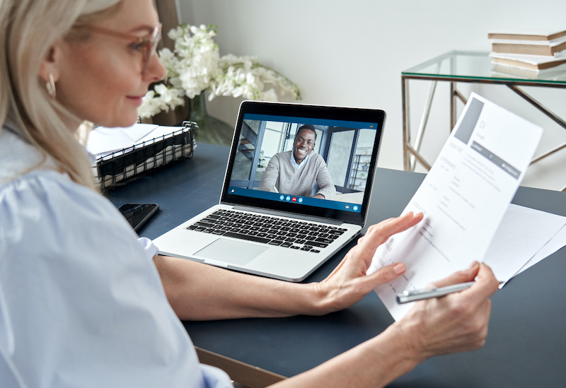 A woman hiring manager conducts a remote interview with a candidate who has had video interview coaching