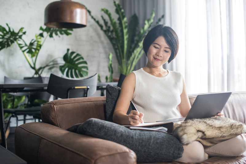 A woman sits on her sofa, using tips from a career coach to search for remote work opportunities..