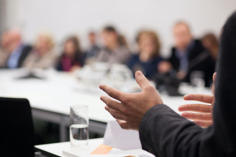 A CEO communicates organizational changes to his company during a meeting.