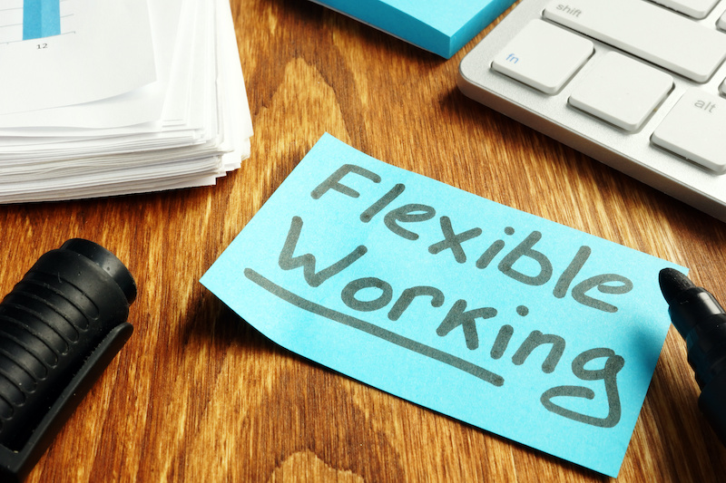 """A sticky note on a desk says """"flexible working"""""""
