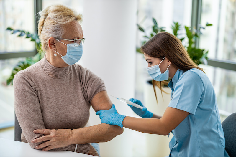 A female employee gets a COVID-19 vaccine to comply with her company's vaccine policy.